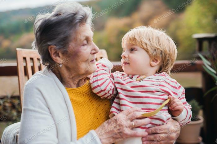 Mujer anciana con un niño bisnieto en una terraza en otoño.