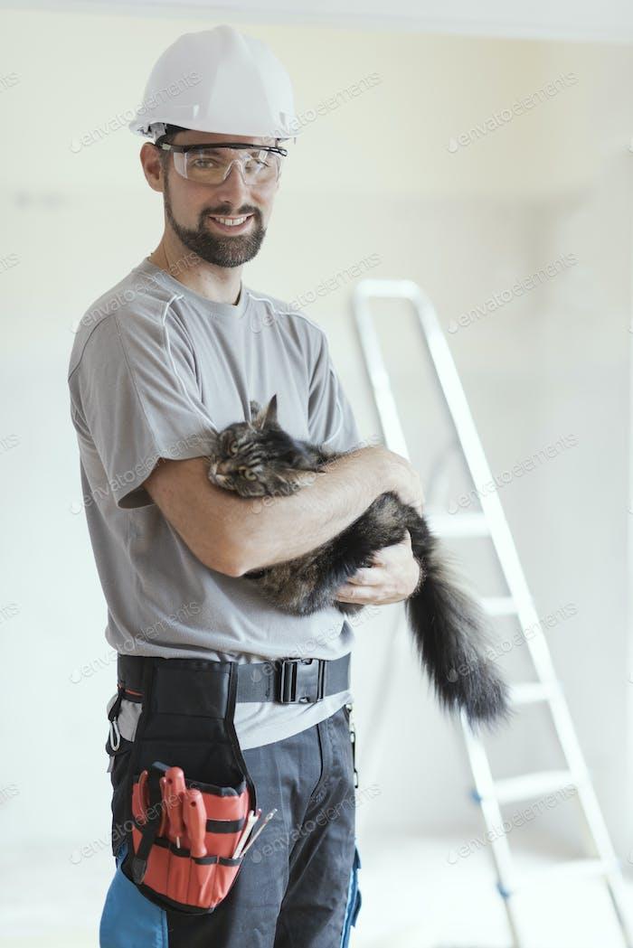 Repairman posing and holding a beautiful cat