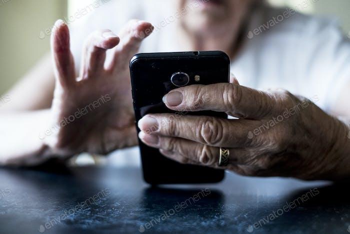 Nahaufnahme der Seniorin sitzt an einem Tisch, mit Handy.