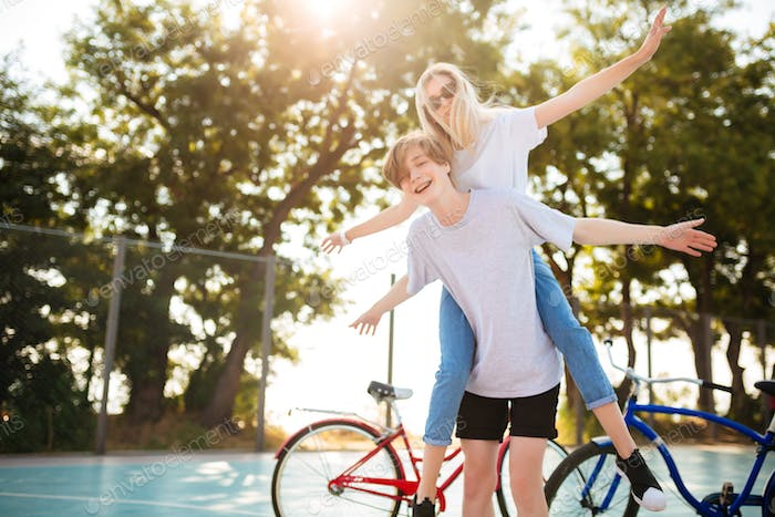 Portrait of young couple having fun together in park with bicycles on background