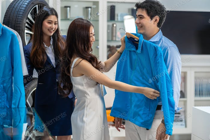 Asian couple choosing and trying the smart clothes to her boy friend in car showroom,
