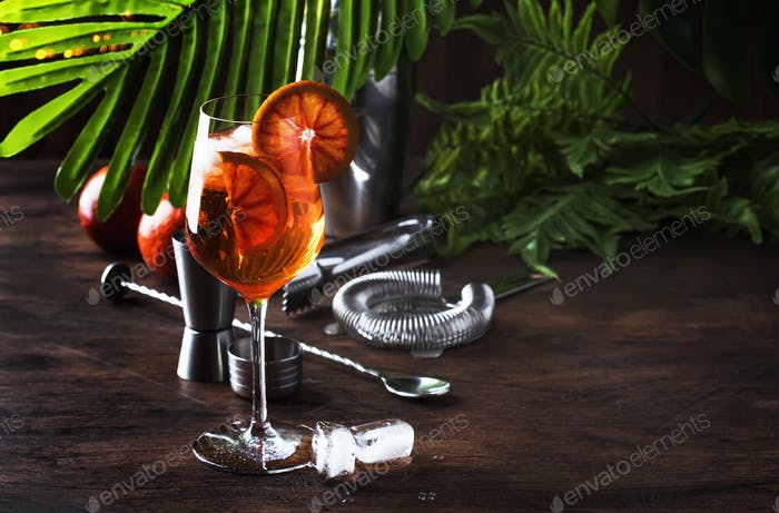 Aperol spritz cocktail in big wine glass with orange slices