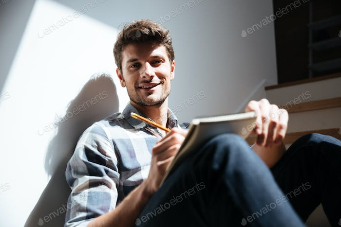 Happy young man sitting the floor and writing in notepad