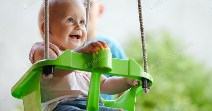 Happy cheerful baby smiling while on swing