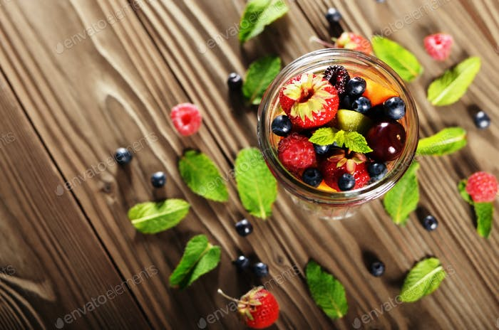 Top view of assorted fruits in mason jar on kitchen wooden table