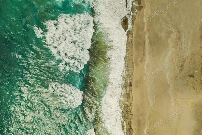 Luftaufnahme von Sand, der das Meerwasser und die Wellen trifft
