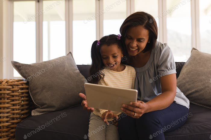 Front view of mother and daughter using digital tablet in living room at home