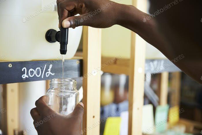 Man Filling Container From Dispenser For Body And Beauty Products In Plastic Free Grocery Store