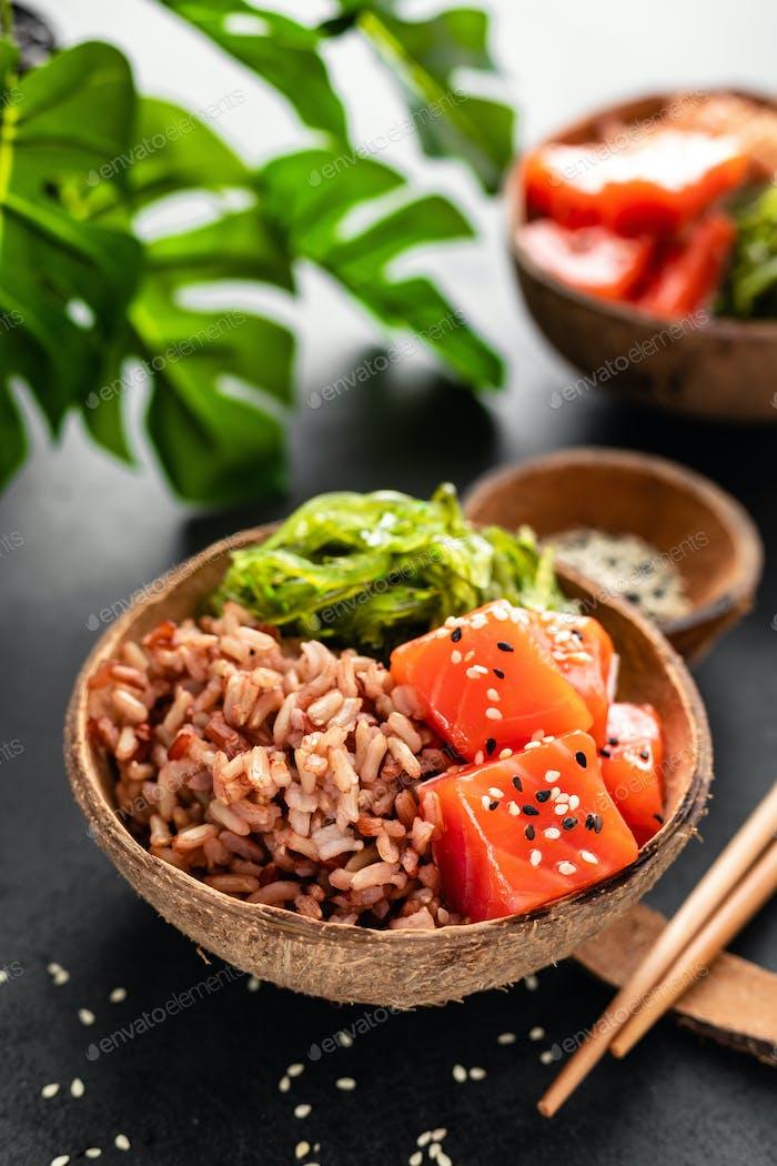 Poke Bowl mit rohem Lachsfisch, Chuka-Salat und Reis in Kokosnussschalen auf schwarzem Hintergrund