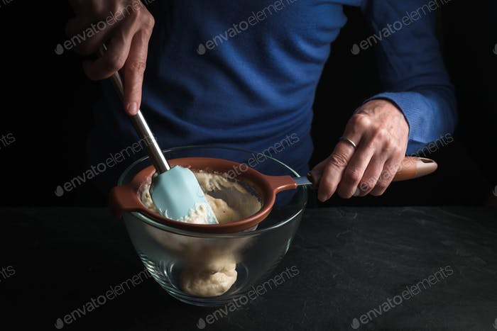 Wiping the Bechamel sauce through a sieve with a spoon