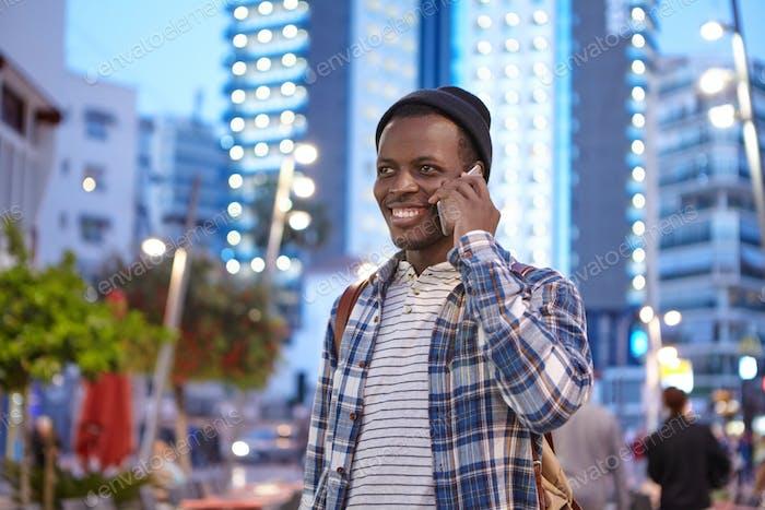 Porträt eines hübschen schwarzen Männchens in Freizeitkleidung und Rucksack, der über dem Hintergrund der Nachtstadt steht
