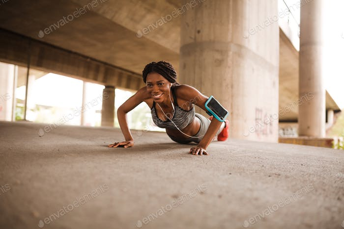 Motivated black woman doing push-ups outdoors