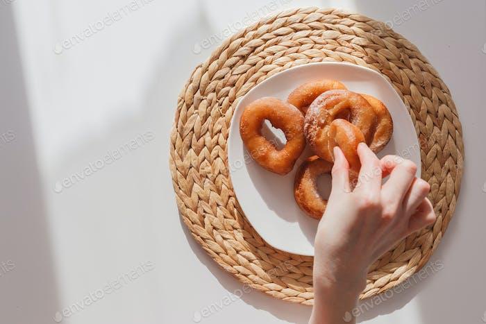 Glutton Mädchen nimmt Donuts von einem Teller eins nach dem anderen. Mädchen Hand und Teller mit Donuts. Ansicht von oben