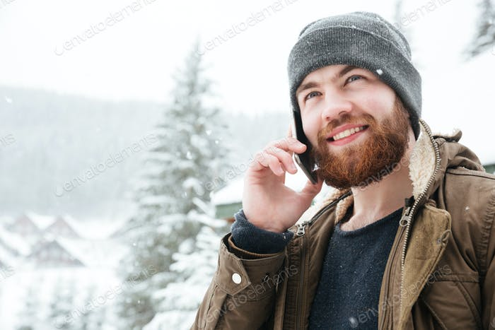 Handsome man talking on mobile phone outdoors in winter