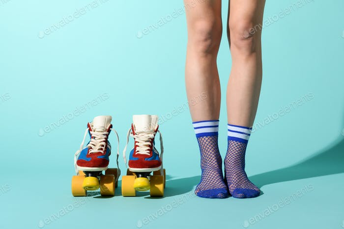Woman in sexy blue fishnet anklets with roller skates