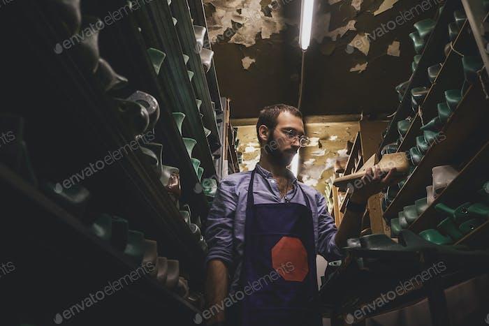 Cobbler in glasses at shoe form storage