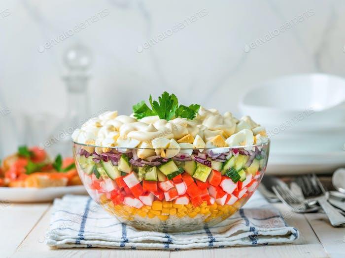 Layered crab salad with corn, cucumber, rice
