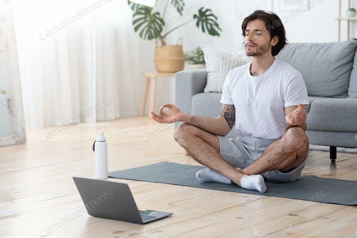 Konzentrierter junger Mann sitzt in Lotus-Pose