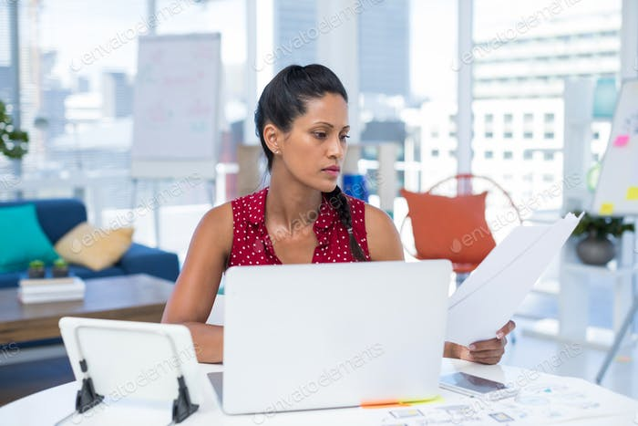 Female executive looking at documents while working at desk