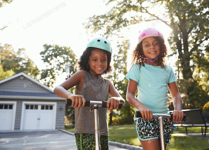 Bruder und Schwester Reiten Roller auf Auffahrt zu Hause