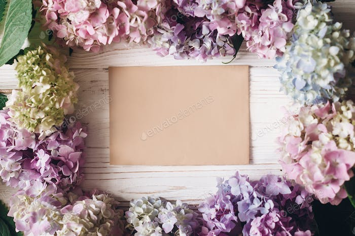 Beautiful hydrangea flowers and paper greeting card on rustic white wood