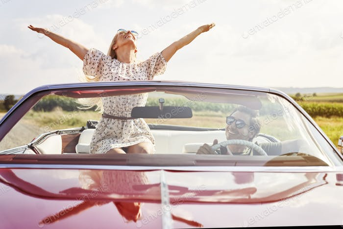 Front view of happy young people in a cabriolet