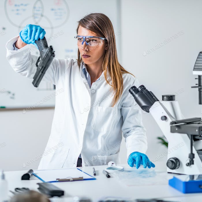 Forensic science expert examining gun collected at a crime scene