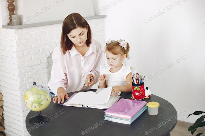Tutor with litthe girl studying at home