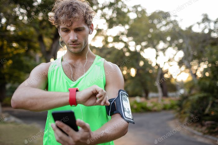Jogger listening to music on mobile phone and checking his smartwatch