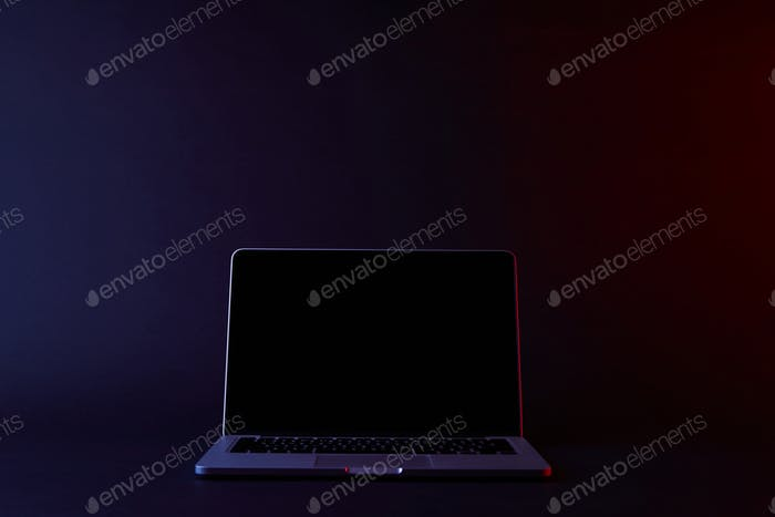 one turned off laptop on dark surface