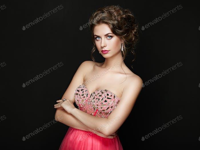 Fashion portrait of beautiful woman in elegant dress