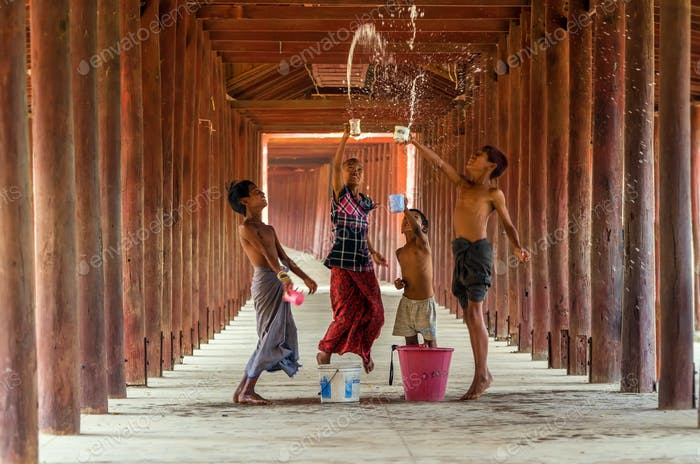 Burmese children playing the water with songkran festival in pagoda