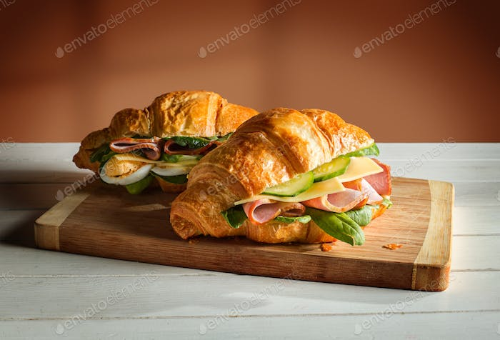 Croissants sandwiches on the wooden cutting board