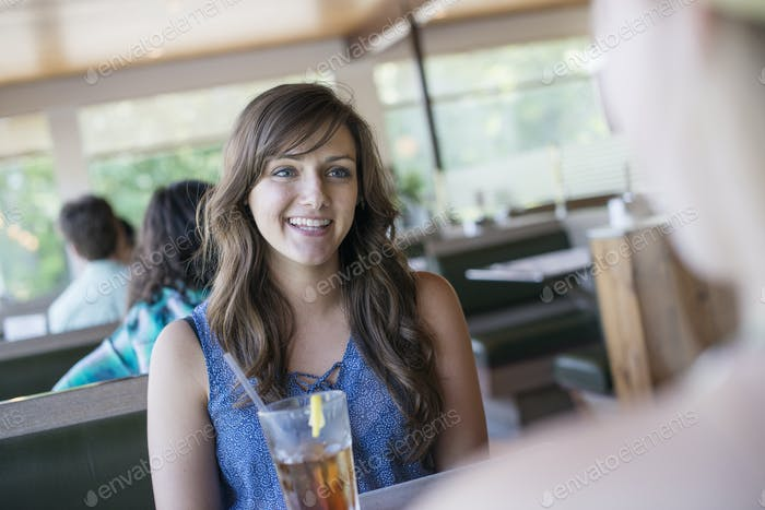 A young woman sitting at a table in a diner with a cool drink.