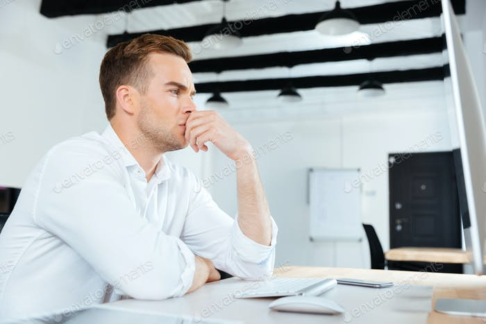 Businesman working with computer and thinking at workplace