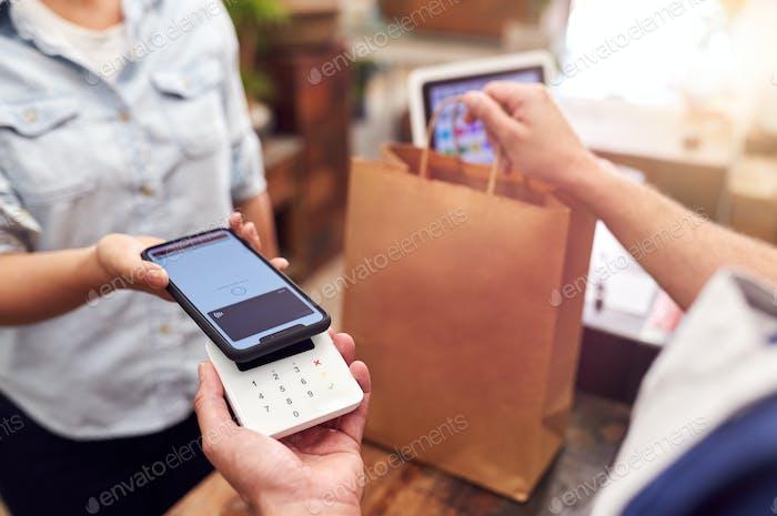 Nahaufnahme der Frau im Geschäft machen kontaktlose Zahlung am Sales Desk Halten Handy An Leser