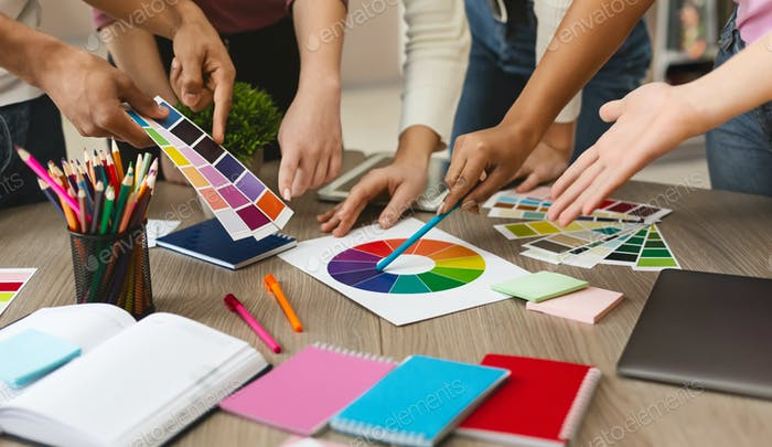 Group of young graphic designers choosing color swatch samples