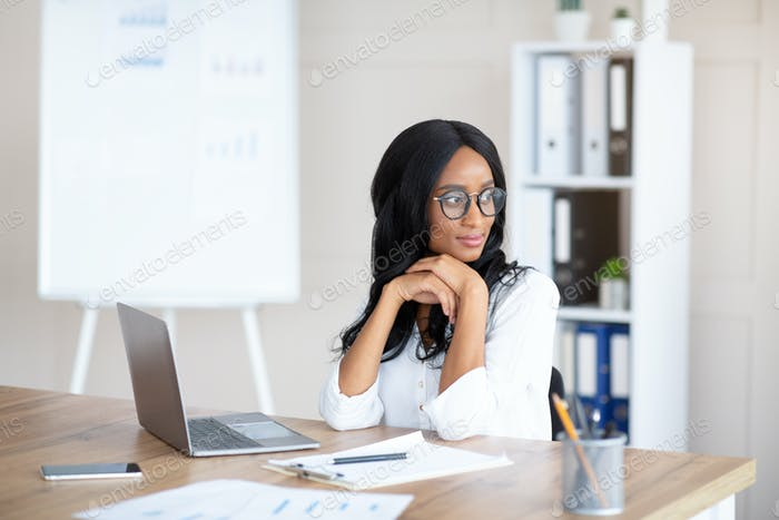 Portrait of young female secretary daydreaming in front of laptop at workplace, copy space