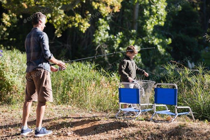 Vater und Sohn mit Angelausrüstung im Wald