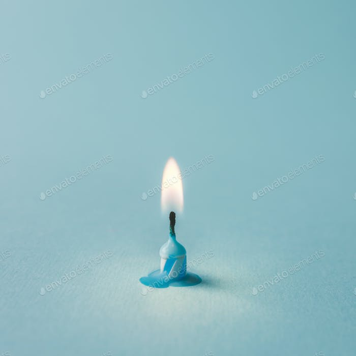 Burnt out candle on blue background. Minimal timeline concept.