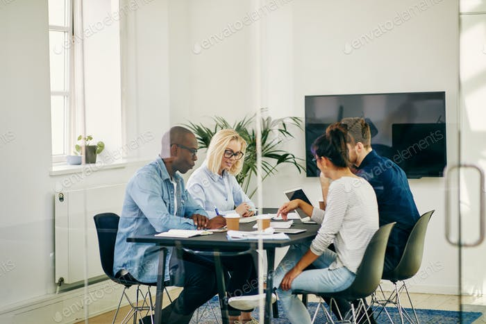 Group of young businesspeople meeting together in a modern office