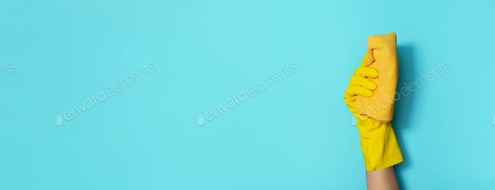 Hand in glove holding microfiber cleaning cloth on blue background. Copy space. Cleaning service