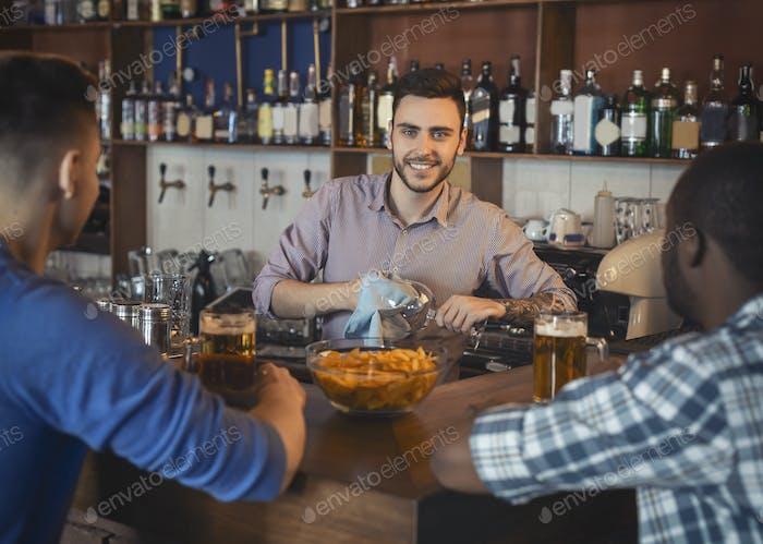 Красивый бармен чистки очки за барной стойкой