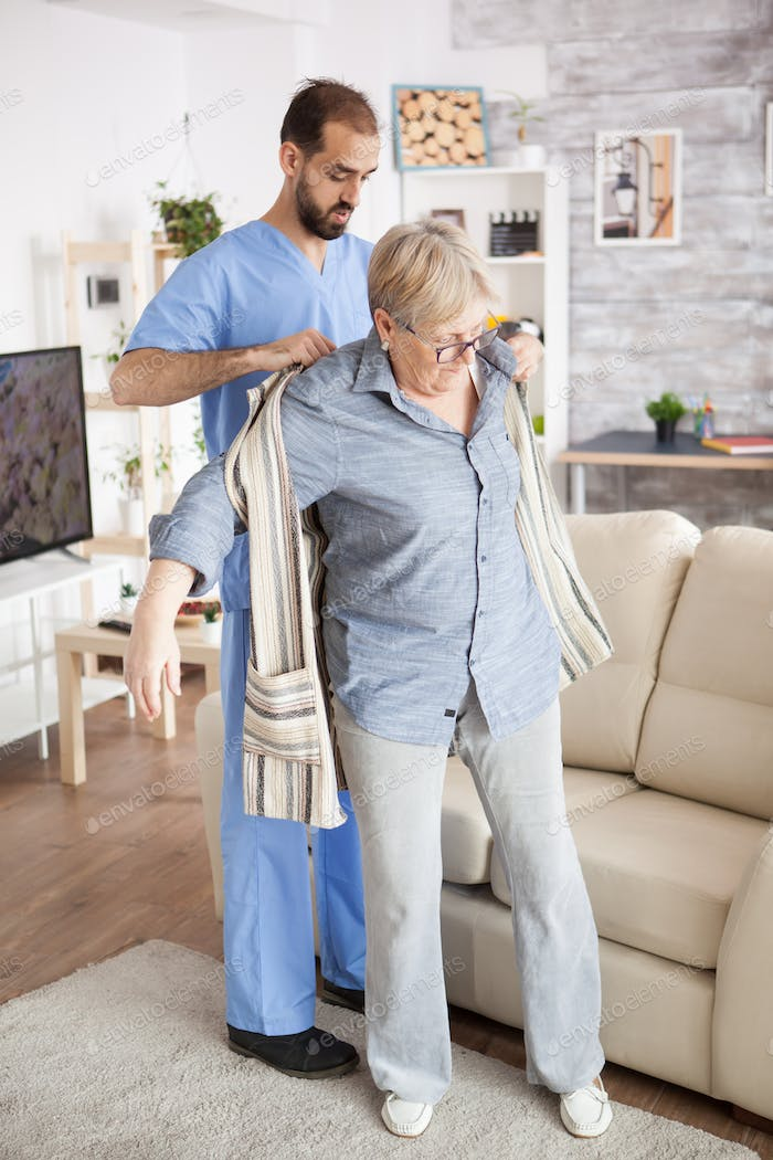 Young male caregiver in nursing home