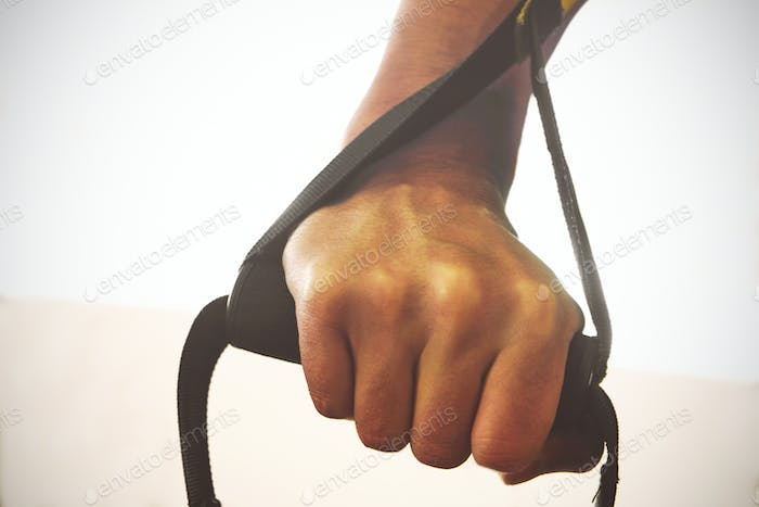 TRX. Male hands with fitness TRX straps in gym.