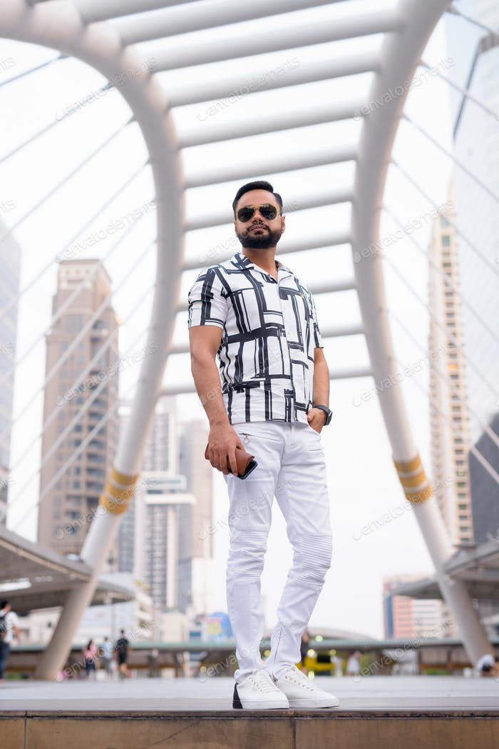 Full body shot of bearded Indian man with sunglasses standing in the city