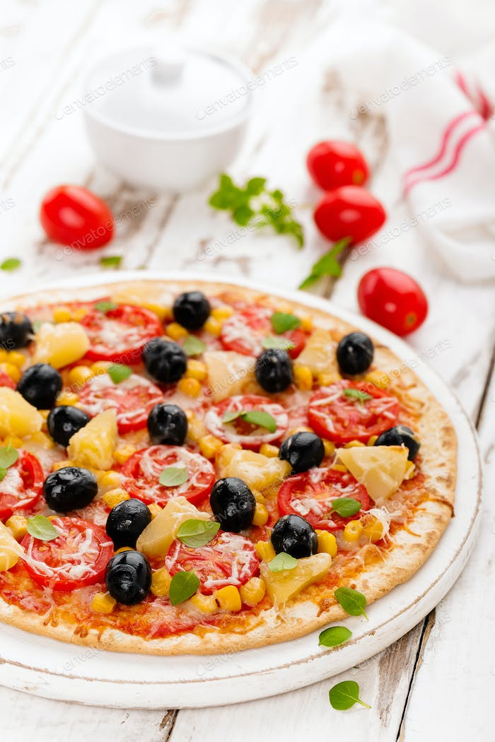 Pizza with tomatoes, mozzarella cheese, olives, corn and basil. Traditional italian cuisine