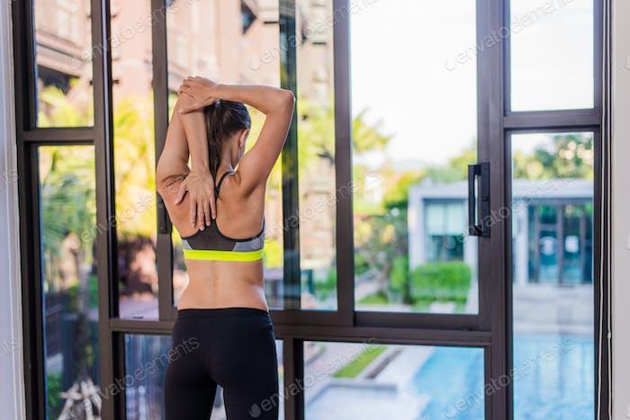 Rückansicht der jungen Frau Stretching tun morgendliches Training im Luxus-Hotel Resort mit einer tollen Aussicht