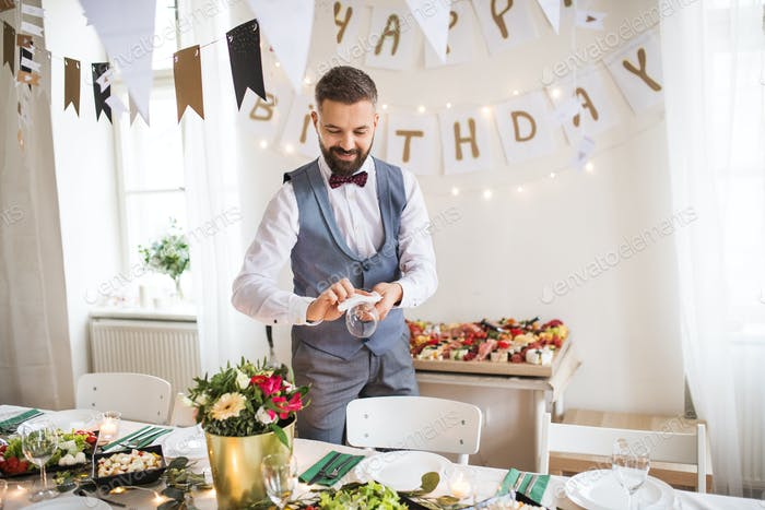 Mature man with bow and vest setting a table for an indoor party.