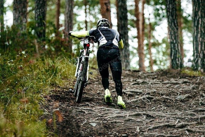 Cyclist Walk Climbs Uphill
